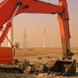 Excavador y molinoes de viento Imagen de archivo