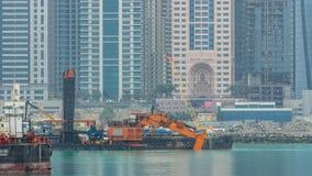 Excavador y rascacielos modernos en la ciudad de Dubai en el timelapse de la mañana de la isla de Jumeirah de la palma almacen de video