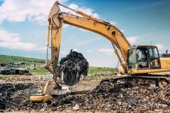Excavadores industriales y maquinaria resistente que trabajan en sitio de la descarga de basura Fotos de archivo libres de regalías