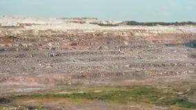 Excavadores y camiones pesados en el granito TILT-SHIFT de la explotación minera de la mina almacen de metraje de vídeo