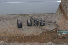 The excavated area around a European telephone distribution box getting ready to be upgraded to fiber optic cable. The excavated area around the bottom of a Royalty Free Stock Images