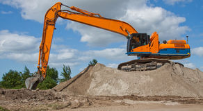 Excavating. An excavator waiting for a dumptruck stock photography