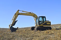 Excavating backhoe in field Royalty Free Stock Photo