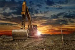 Excavating machinery at the construction site. Copy space. Excavating machinery at the construction site, sunset in background. Copy space for your text royalty free stock image