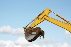 Excavation. The mechanical arm of an excavator and its bucket with soil  are isolated against a blue sky in a conceptual image for construction, industry and Royalty Free Stock Photos