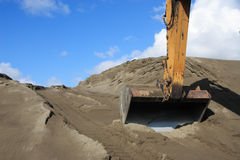 Excavation. The front of a backhoe Excavator digging in the soil Royalty Free Stock Photography