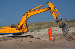 Excavation. An engineer in orange suit and helmet near a earth moving machine. Safety first Royalty Free Stock Photography