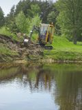 Excavation. Earth mowing near the pond with small excavator Royalty Free Stock Images