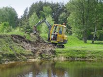 Excavation. Earth mowing near the pond with small excavator Stock Photography