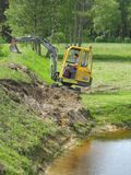 Excavation. Earth mowing near the pond with small excavator Stock Photos