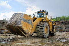 Excavation with a big stone. In a granite quarry Royalty Free Stock Photo