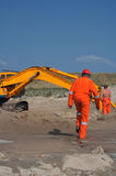 Excavation engineer. An engineer in orange suit and helmet walking to an earth moving machine. Safety first Stock Image