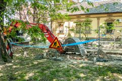 Excavation machinery excavate ground from street in the shade for new district heating pipe line.  stock photo
