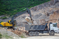 Excavation in the mountains. Excavator puts a huge stone in the truck Royalty Free Stock Images