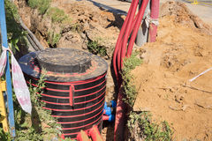 Excavation pit. Electrical cables and optical fibres in the digging on a construction site Royalty Free Stock Photo