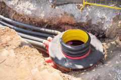 Excavation pit. Electrical cables and optical fibres in the digging on a construction site Stock Photo