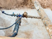 Excavation pit. Old 500mm drink water pipe with 150mm  cornering arm with gate valves, corroded  joining fittings.  Tubes before r Royalty Free Stock Photo