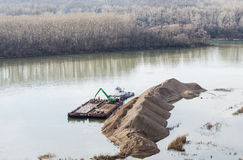 Excavation on the river. Construction vehicles strengthens the coastline on the river Royalty Free Stock Photos