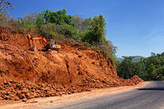 Excavation for Road Widening. Massive earth cutting using heavy construction and earth moving hydraulic equipment being done for widening highway in a hilly Stock Photography