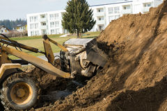 Excavation in soil heap at a construction site. Loader shovels in a pile of dirt at a construction site earth royalty free stock image