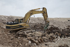 Excavation in stone. Machine with hammer for excavation in rocky terrain Royalty Free Stock Photos