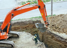 Excavation work. Excavator works on a sight supervised by worker Stock Photography
