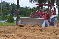 Excavation Work Series 2. A red tractor busy with excavation work at a construction site Royalty Free Stock Image