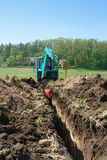 Excavation works. Digger digging waterline trench in the field Stock Photo