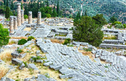 Excavations of the ancient Delphi city (Greece). Excavations of the ancient Delphi city along the slope of Mount Parnassus (Greece). The amphitheater and columns Royalty Free Stock Photo