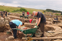 Excavations at Roman Vindolanda. ROMAN VINDOLANDA-ENGLAND - JULY 12: Unidentified archaeologists & summer students participate in excavations at an ancient Roman Royalty Free Stock Image