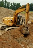 Excavator 1. Heavy equipment excavator digging into clay soil – vertical image Stock Photos