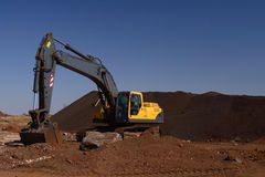 Excavator. Yellow excavator with blue background royalty free stock photos