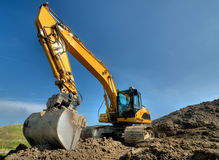 Excavator. On a construction site on a sunny day Stock Photos