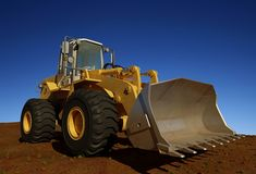 Excavator. Standing in quarry with risen bucket over cloudscape sky Royalty Free Stock Images