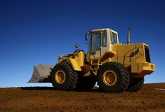 Excavator. Standing in quarry with risen bucket over cloudscape sky Royalty Free Stock Photos