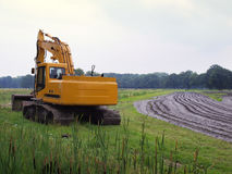 Excavator. Plowed wet muddie farm field Stock Images