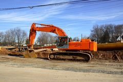 Excavator. Side view of an orange excavator at a construction site near a power line tower Stock Photography