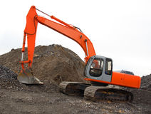 Excavator. An orange excavator parked on a hill of dirt Stock Image