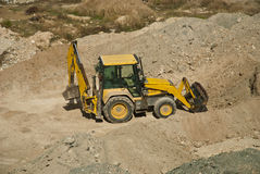 Excavator. A yellow excavator working on sand and earth Royalty Free Stock Photography