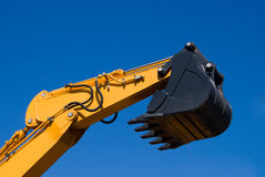 Excavator. Yellow hand of power-shovel with a black scoop on a background blue sky Royalty Free Stock Photo