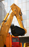 Excavator. New yellow excavator with a black digging bucket Stock Image