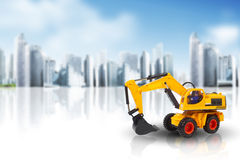 Excavator against a cityscape Royalty Free Stock Images