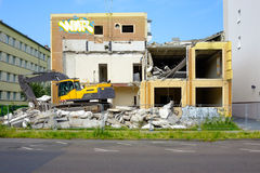 Excavator alongside abandoned building ready for demolition Royalty Free Stock Images