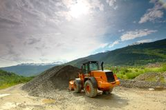 Excavator in alps Stock Photography