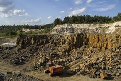 Free Excavator And Basalt Columns Rocks. Heavy Industry. Stone Excavation. Producing Stone From Basalt Pillars. Stock Photos - 106583633