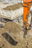 Excavator arm with bucket full of dirt Stock Images