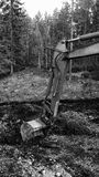 Excavator arm digging in mud monochrome. Excavator arm digging in mud background black and white royalty free stock photography