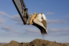 Excavator arm and scoop digging dirt. At construction site against blue, partially cloudy, sky Stock Images