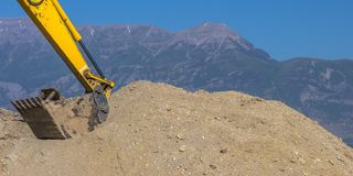 Excavator arm scooping dirt in front of mountain royalty free stock image