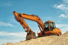 Excavator as bace to top construction. Powerful excavator at raising level of construction site. The shovel bucket is leaned on the earth and arm is holding the Stock Photo